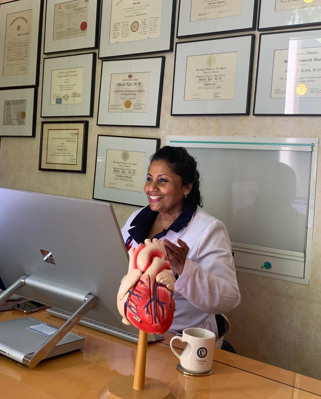 Dr. Sheila Kar looking on computer screen Photo